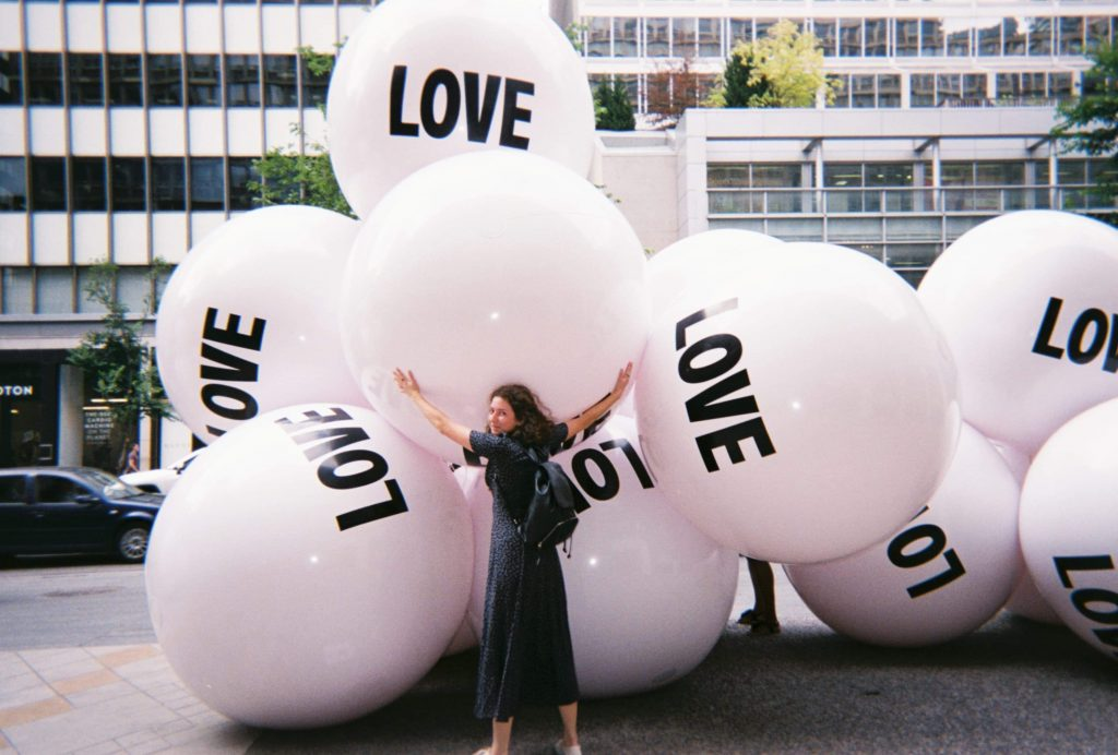 "Olive hugging balloon balls that say ""love""."