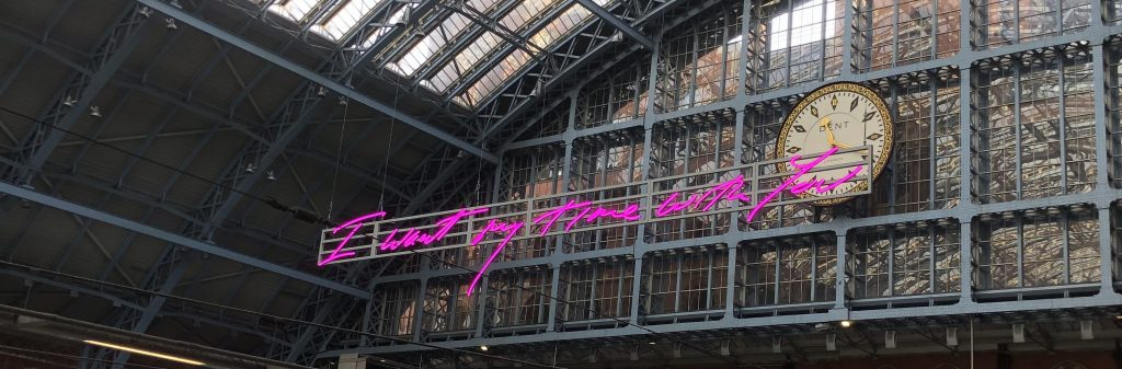 "A pink neon sign that reads ""I want my time with you"" in St. Pancras Station, London."