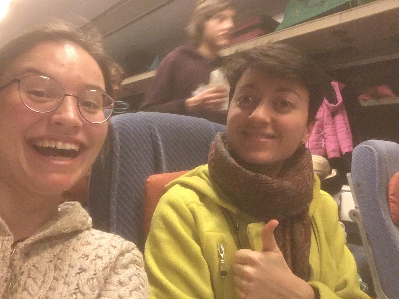 Claire and Aline smile with thumbs up, sitting in two seats on a busy train