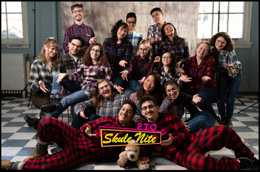 "Group of students wearing flannel with ""Skule Nite 2T0"" logo in the bottom middle"