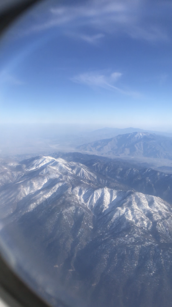 Picture of mountains taken through an Airplane window. There is snow on the tops of the mountains and a vast landscape