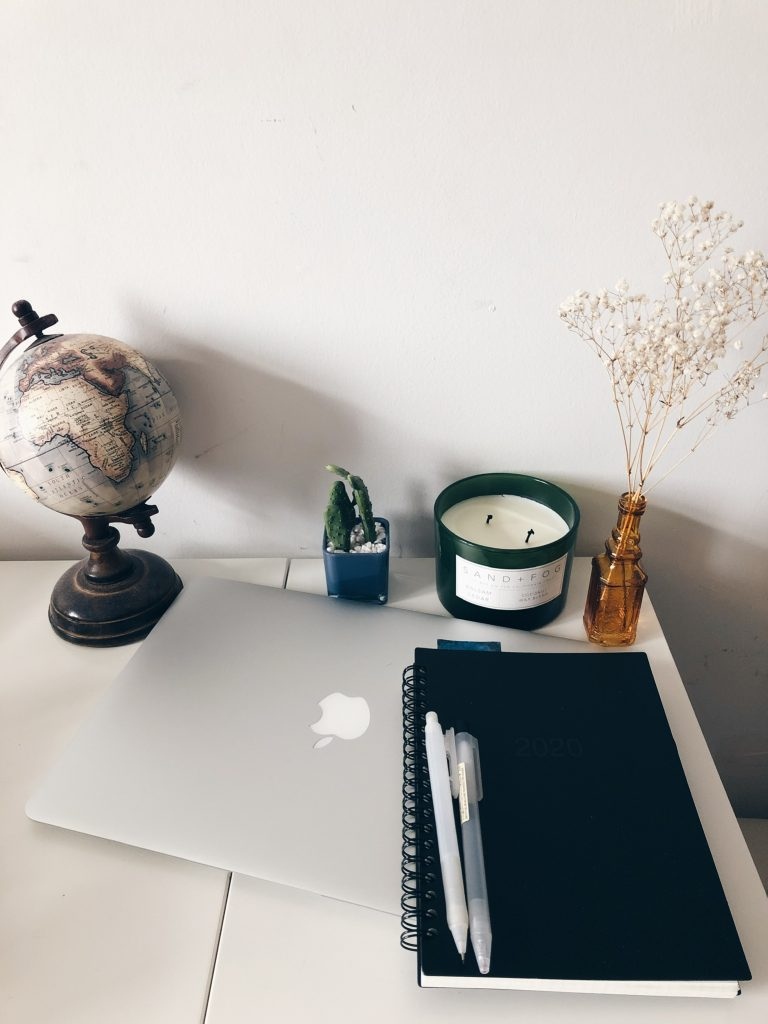 Picture of my laptop, a globe, candle, and agenda