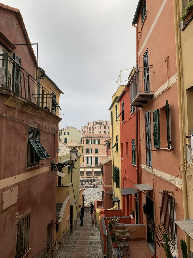 An image of a narrow street in Italy with colourful houses.
