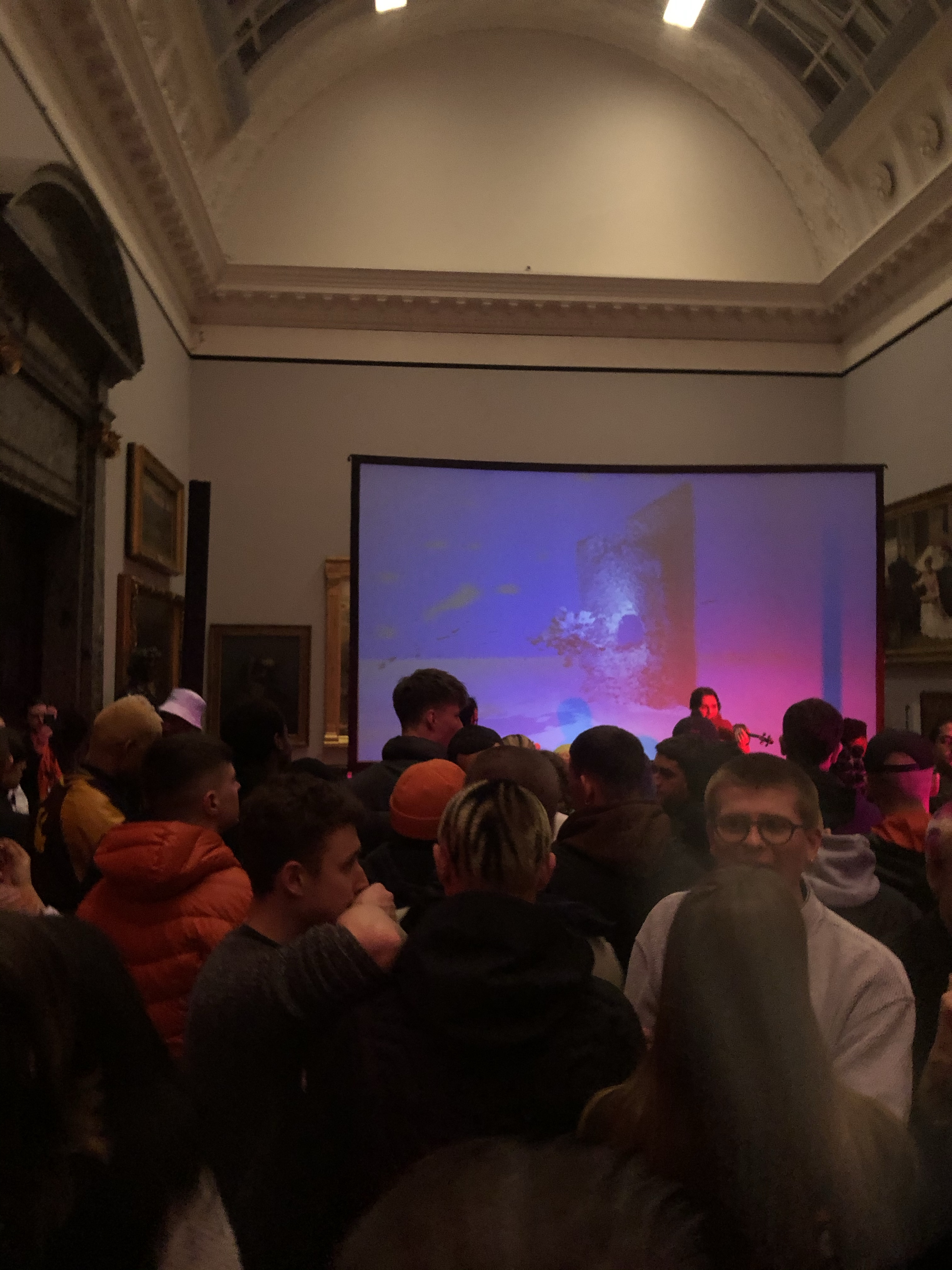 A room in the Tate Britain with pink and blue lights. The room is full of young people