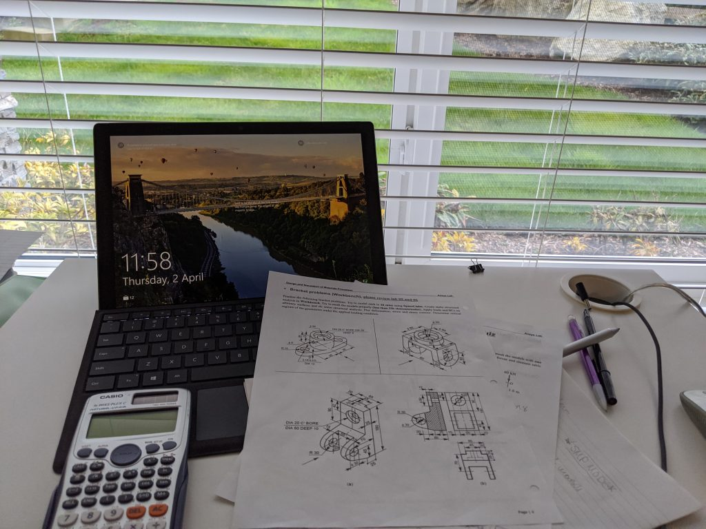 Open laptop with pages with diagrams and a calculator in front