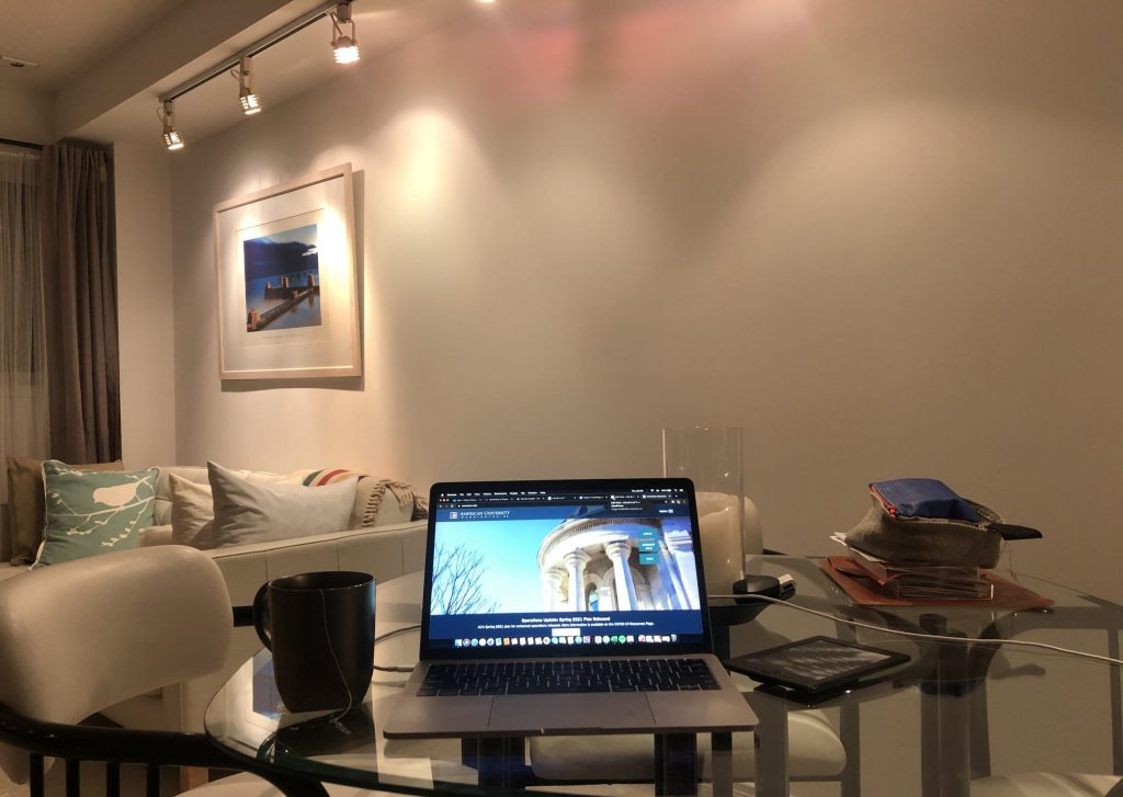Picture of a laptop screen showing the American University homepage. The laptop sits on a table in the living room