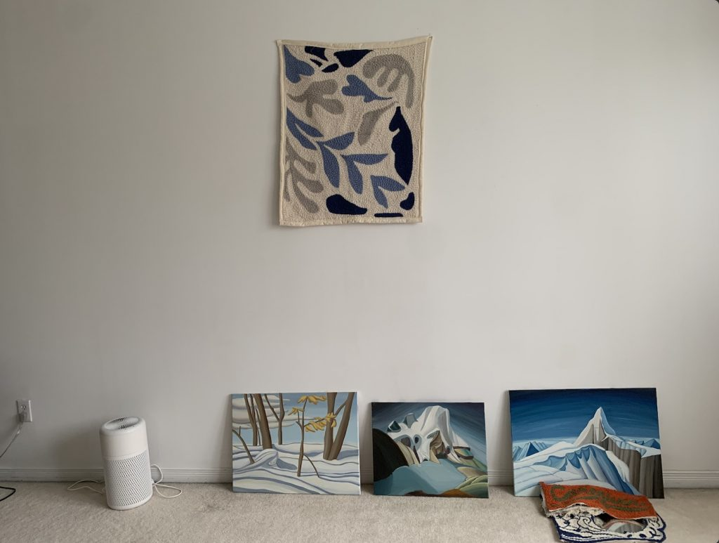 three paintings leaning against a wall, with a rug pinned on the wall