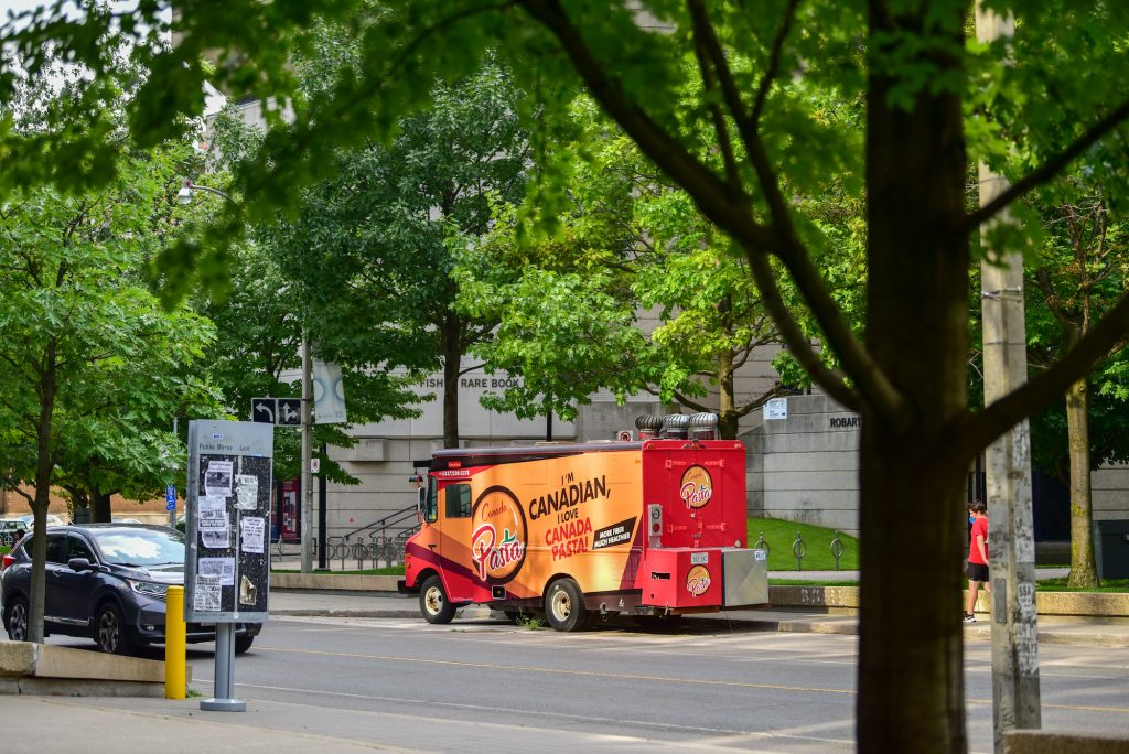 red food truck outside Robarts library,  surrounded by green trees and leaves