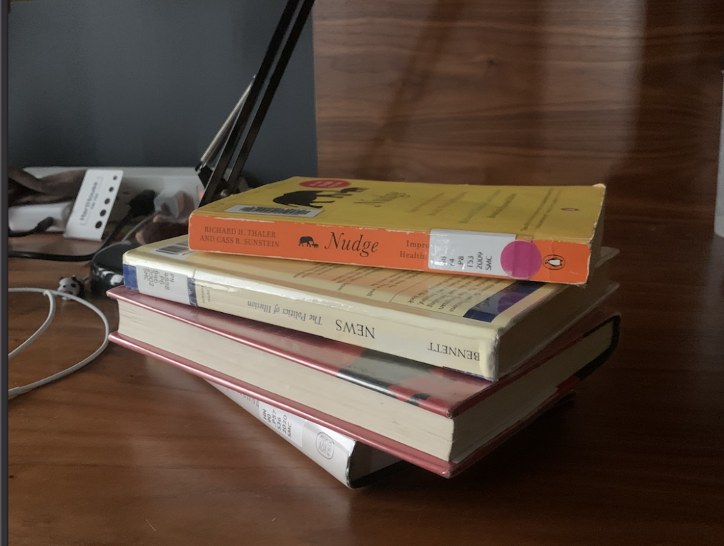 a stack of library books on a desk